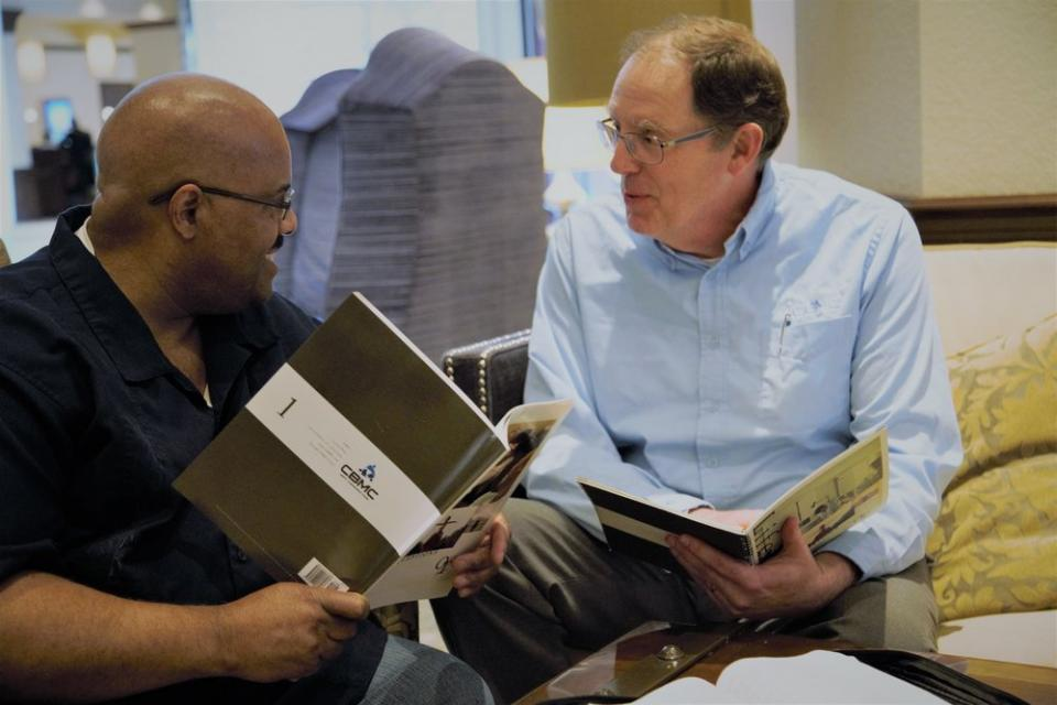 two men discussing OT with books